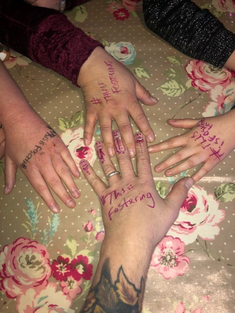 This couple have been fostering for 5 years. The siblings they look after have been with them for a year. #ThisIsFostering is a campaign run by the fostering network to raise awareness of fostering. The family in this picture have #ThisIsFostering written on their hands.