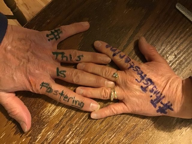 A photograph of a fostering couple for #ThisIsFostering. The photo shows their hands intertwined with #ThisIsFostering written on them.