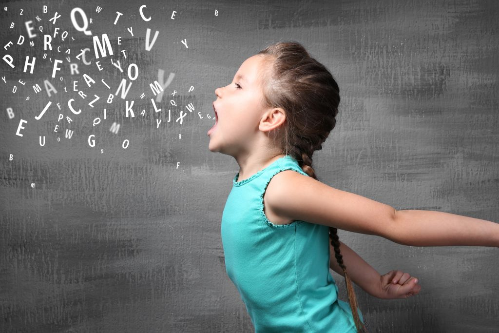 A young girl with plaited hair and a green dress is opening her mouth, letters pour out of her open mouth. This represents the need for foster carers to help give children a voice.